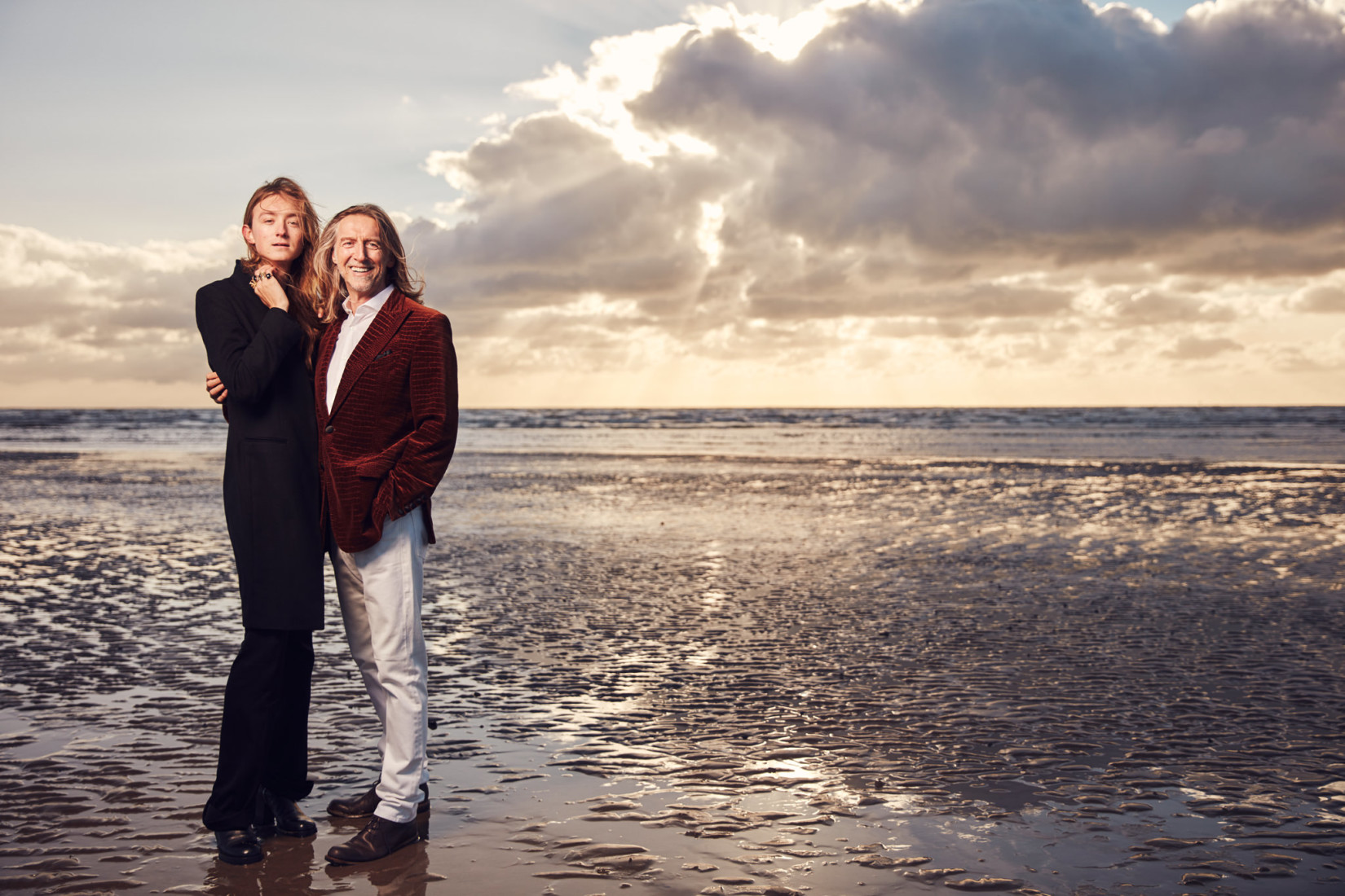 Nic and Harris Reed embrace on the beach in front of a sunrise