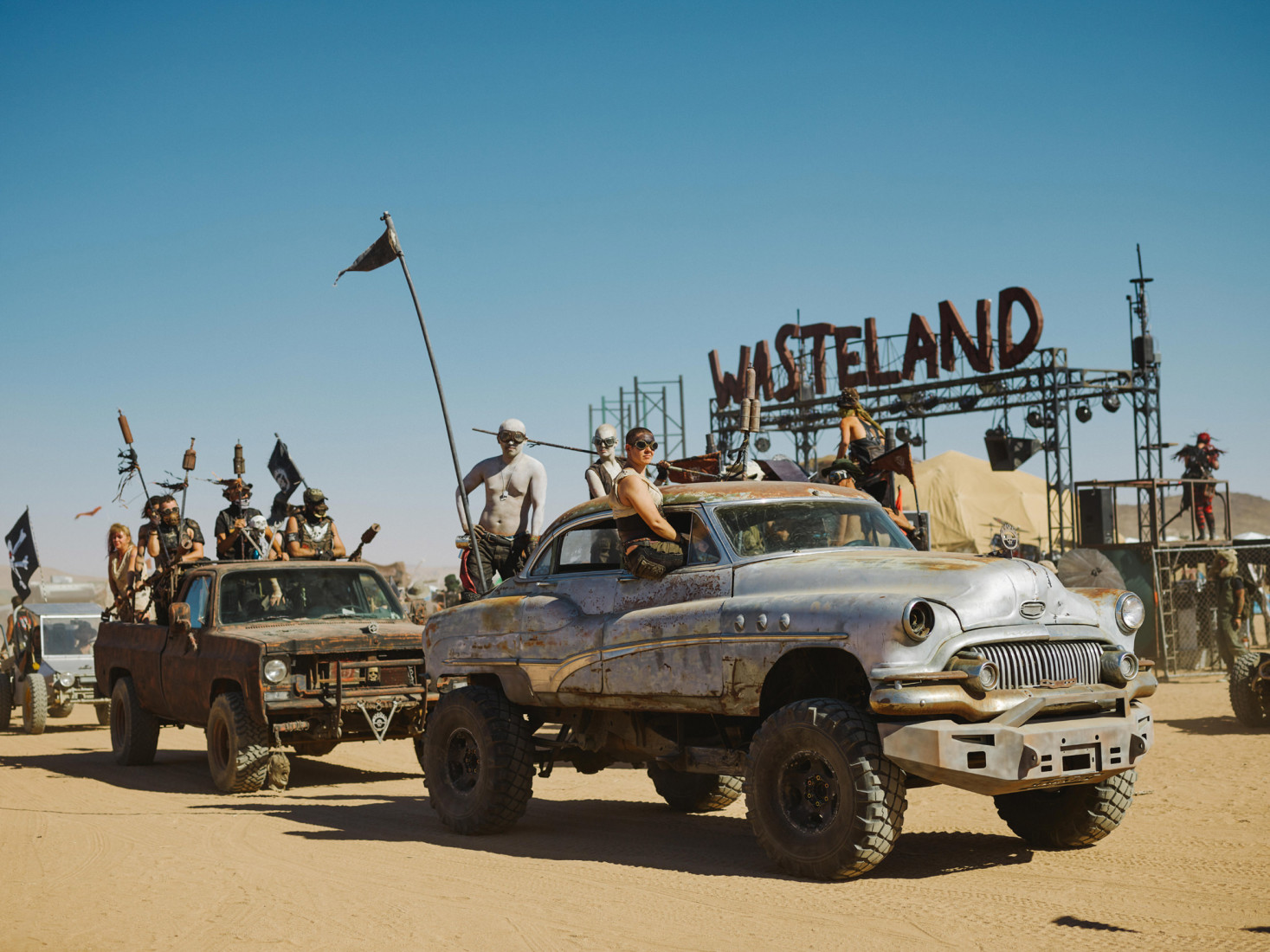 Procession of cars in front of the main sign at Wasteland Weekend festival